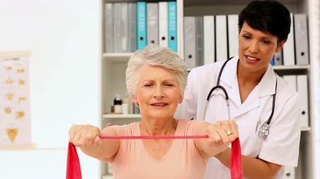 fizjoterapeuta : Nurse showing elderly patient how to use resistance band in office at the hospital Wideo