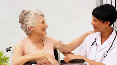 dialog : Nurse talking with elderly patient in a wheelchair in office at the hospital