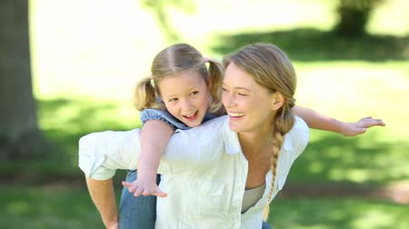проведение : Happy little girl getting a piggy back from mother in the park on a sunny day