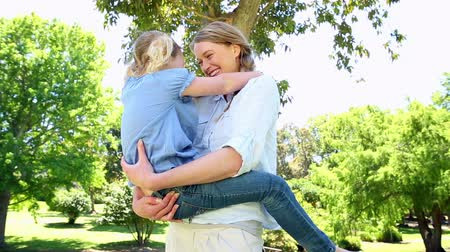 transportar : Happy mother holding her little girl in the park on a sunny day Stock Footage