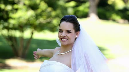esinti : Beautiful bride smiling at camera in the park on a sunny day