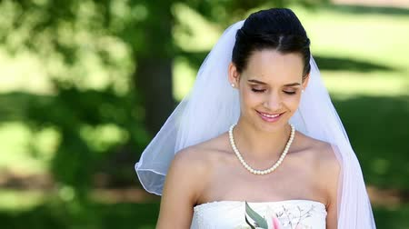 bouquets : Beautiful bride smiling at camera in the park on a sunny day