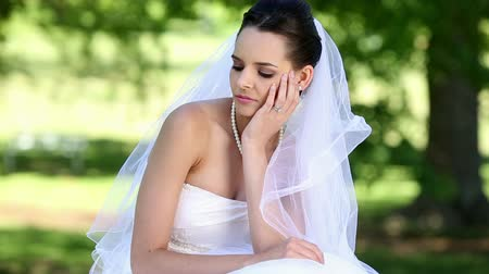 apprehensive : Upset bride sitting on the grass on a sunny day