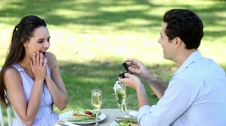 öneri : Man proposing marriage to his shocked girlfriend on a sunny day