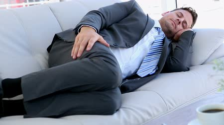podnikatel : Businessman sleeping on the sofa in the office