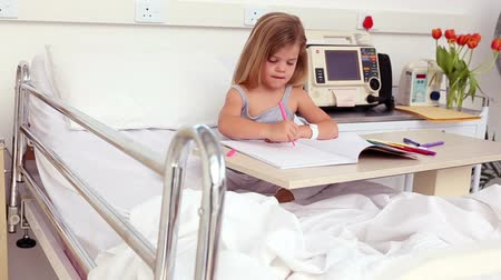 kurtarma : Little girl sitting in hospital bed colouring in the hospital ward