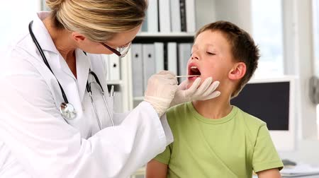 checagem : Doctor checking little boys tonsils in her office at the hospital