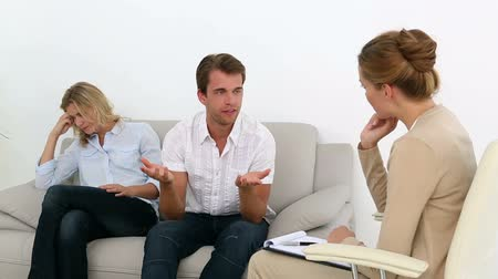 counselling : Unhappy couple talking with their therapist at therapy session Stock Footage