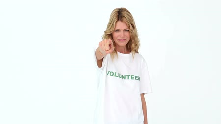 jótékonyság : Pretty volunteer pointing to camera on white background Stock mozgókép