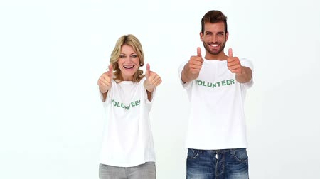 благотворительность : Two volunteers giving thumbs up to camera on white background