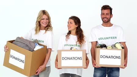 helping : Team of volunteers smiling at camera holding donations boxes on white background