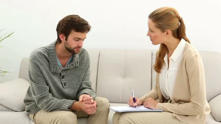 counselling : Young man talking to his therapist at therapy session Stock Footage