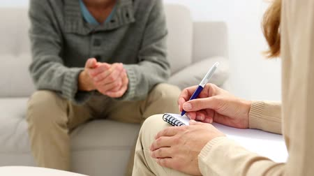 terapeuta : Young man sitting on sofa talking to his therapist at therapy session Stock Footage