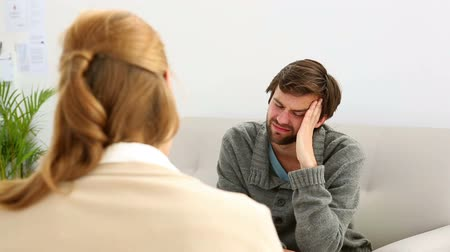 counselling : Young man sitting on sofa talking to his therapist at therapy session Stock Footage