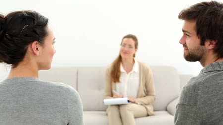 counselling : Therapist smiling at reconciled couple  at therapy session Stock Footage