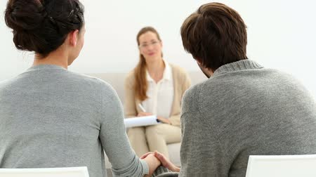 counselling : Therapist smiling at reconciled couple holding hands at therapy session