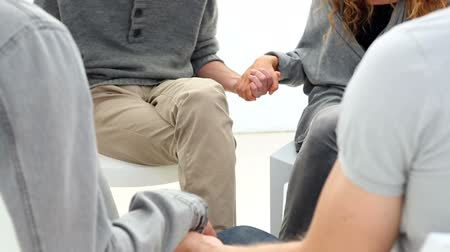terapi : Rehab group sitting in a circle holding hands at group therapy session