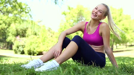atletismo : Fit blonde taking a break in the park sitting on the grass on a sunny day