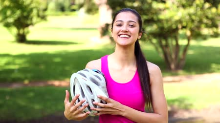 helmets : Fit girl taking off her bike helmet smiling at camera on a sunny day Stock Footage