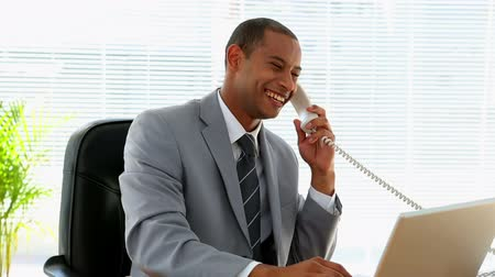 Happy businessman talking on the phone in his office Vídeos
