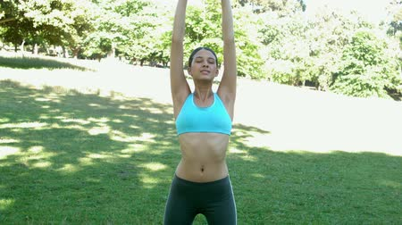 braços levantados : Fit brunette doing yoga in the park in slow motion