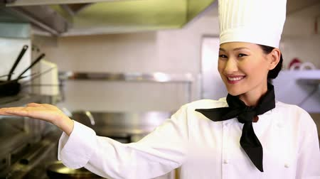 sporák : Happy chef smiling at camera holding her hand out in presentation in commercial kitchen
