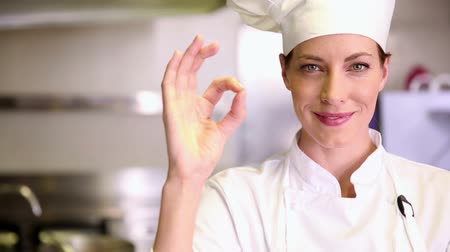 chef : Pretty chef smiling at camera and giving thumbs up in commercial kitchen Stock Footage