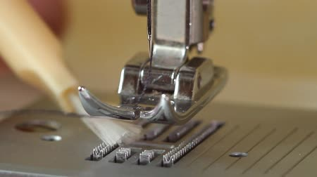 presser : Cleaning the conveyor and sewing machine feet from debris Stock Footage
