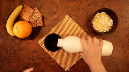 pour out : Female hands pouring yogurt drink in a brown cup near the fruit and cheese, top view