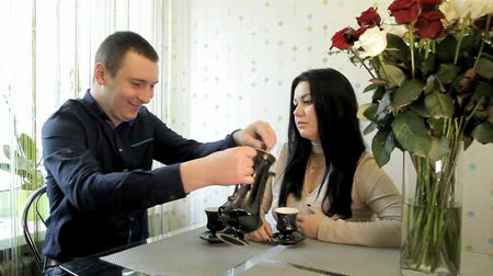 konvice : newlyweds are sitting at a table with a bouquet of roses and pouring tea