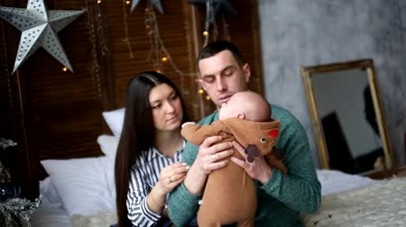 young couple sitting on the bed holding the baby near the Christmas tree
