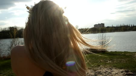 girl with long blond hair talking on the phone on the background of the river