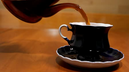 no hands : in a blue cup and a saucer pour tea from a transparent teapot Stock Footage