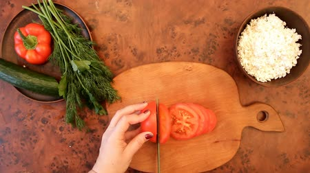 female hand slices a red tomato with a green knife on a wooden board
