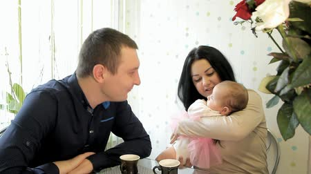 young couple sitting at a table taking a child