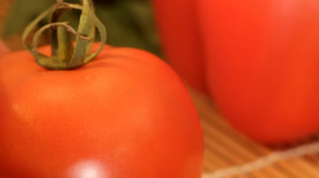 the red tomato is lying next to the sweet pepper, especially close-up