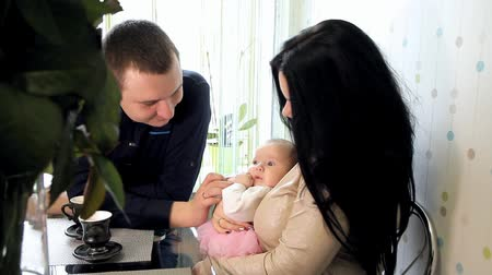 young couple with a baby sitting at the table