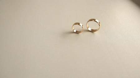 two wedding ring rolling on the white surface