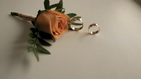 two wedding rings roll on a white surface next to a rose