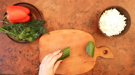 вегетарианство : female hands cut a cucumber on a wooden board, top view
