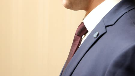 a man in a blue business suit is standing in profile, close-up