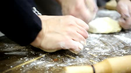 two pairs of female hands knead the dough on a wooden board Dostupné videozáznamy