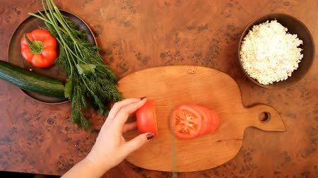 female hands cut a tomato with a green knife on a blackboard