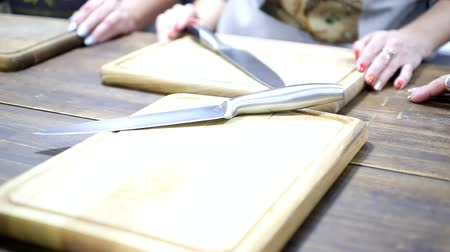Womens hands, metal knives and cutting boards in a professional kitchen, close-up