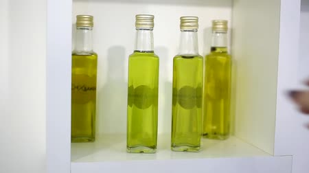 kochanka : a female hand takes a transparent bottle with olive oil from a white shelf