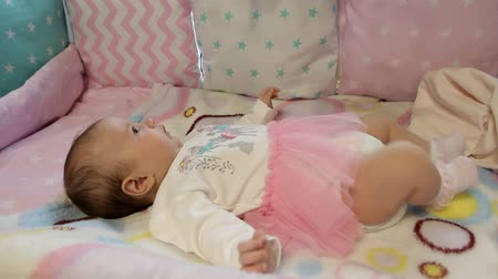 átlagos : baby in a smart dress lies in a crib Stock mozgókép