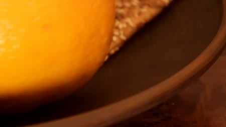 especially : crackers, orange and banana on a clay plate, movement, especially close-up