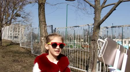 relieves : little girl in sunglasses comes and relieves herself selfie phone, along the fence Stock Footage