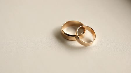 обряд : two wedding rings on a white background, moving camera