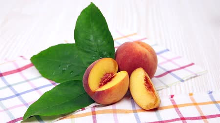 nektarinka : peaches, ripe peaches with a green leaf on a napkin Dostupné videozáznamy
